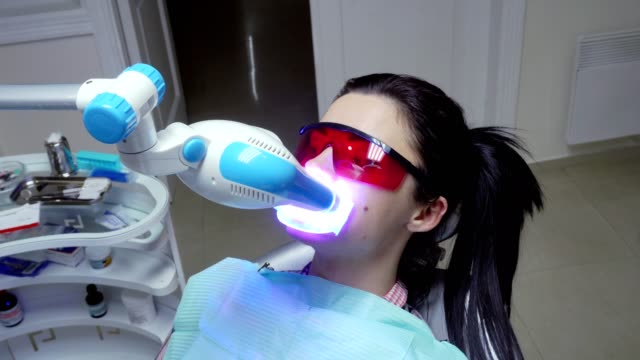 Young woman with an expander in mouth and red protective glasses getting UV whitening. An ultra violet whitening machine in operation on a patient's teeth video