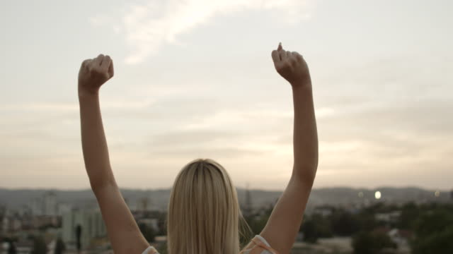 Young woman with arms raised video