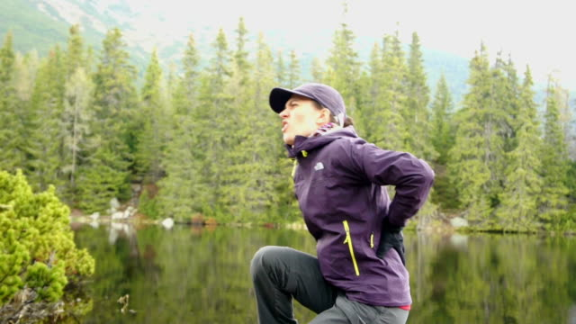 Young woman with back pain in the mountains video