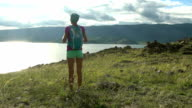 Young woman with backpack walking round mountains and lake video