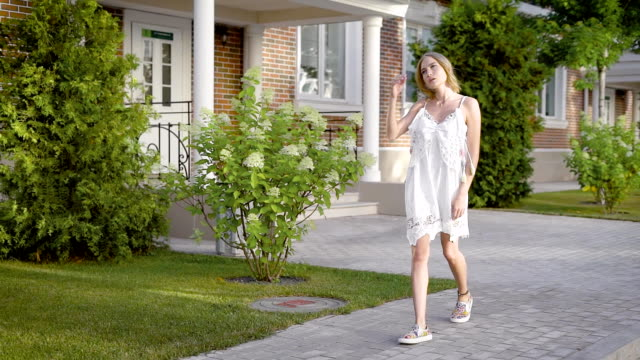 A young woman with blond hair dressed in a white designer dress elegantly walks down the street during the day video