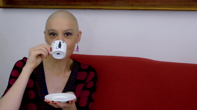 young woman with cancer relaxing and having coffee on the sofa at home video