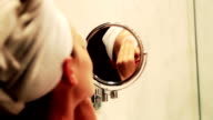 Young woman with cotton pads in the bathroom video