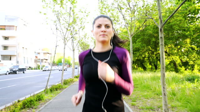 Young woman with earphones running on the sidewalk. video