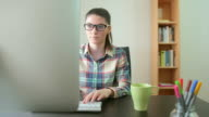 Young woman  with eyeglasses in front of the computer. video