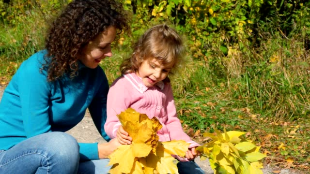 Young woman with girl take good look at maple leaves video