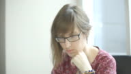 Young woman with glasses looking intently at laptop screen, leaning her chin on her hand video