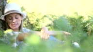 Young woman with hat relaxing in forest video
