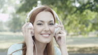 Young woman with headphones in park video