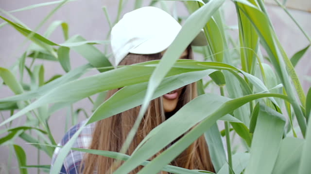 A young woman with long hair in a baseball cap stands in the middle of a tall grass. He looks at the camera and smiles. video