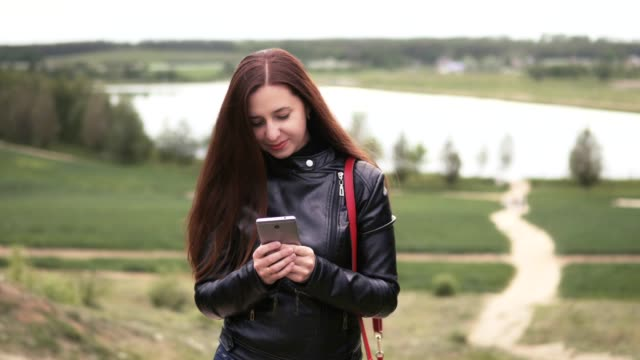 Young woman with long hair is using a mobile phone in nature. Against the background of the lake video