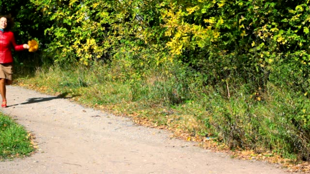 Young woman with maple leaves running in autumn park video