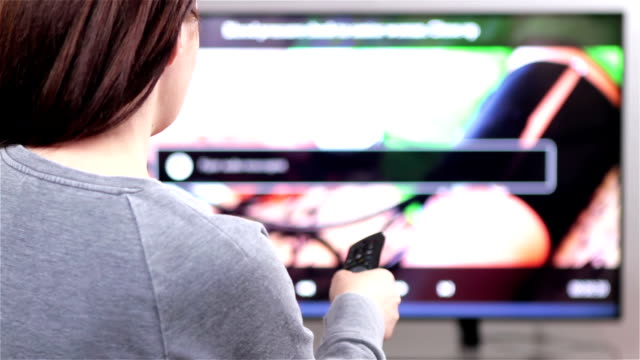 Young woman with remote control watching smart TV video