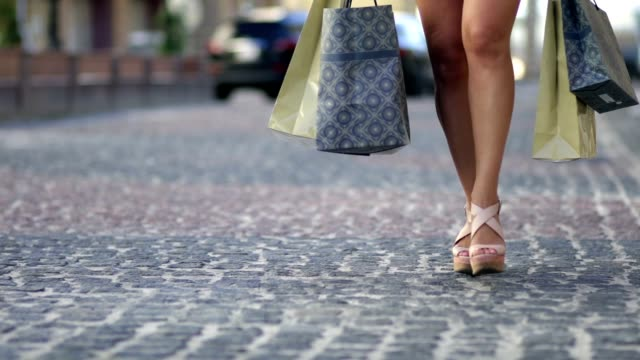 Young woman with shopping bags walking city street video
