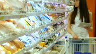Young woman with shopping cart buying refrigerated groceries at the supermarket and using tablet pc to check shopping list. Girl coming up to the fridge in shop and taking product from it video