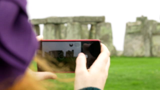young woman with smartphone making photos to stonehenge video