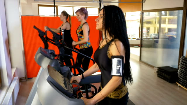 Young woman with smartphone tracker arm strap exercising in the fitness gym with friends video