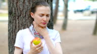 Young woman with sore throat eating apple video