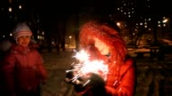 Young woman with sparkler, near little girl, night outdoor video