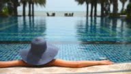Young woman with straw hat on the pool video