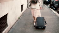 Young woman with suitcase and backpack going through the building in the city. Girl with baggage moving to new place video