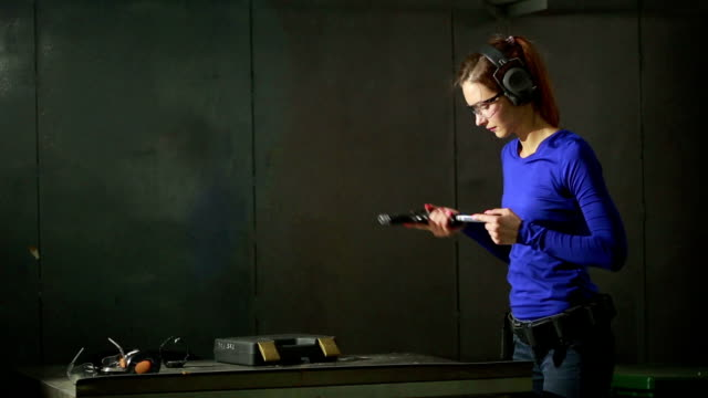 young woman with the gun on an indoor shooting range. collect gun video