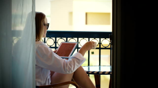 Young woman with touchpad on hotel balcony video