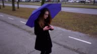 Young woman with umbrella using smartphone video