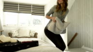 Young woman with wavy long light brown hair at home in the morning put a grey towel in the luggage on the bed - HD video footage video