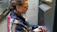 Young woman withdrawing money from ATM machine video