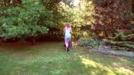 young woman work with grass cutter on own green garden. FullHD video