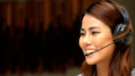 Young woman working in a call centre using a headset video