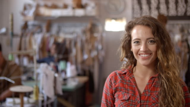 Young woman working in design studio walks in to focal plane video