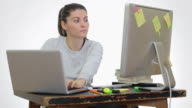 Young woman working in front of the PC and laptop in the same time . video