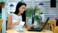 Young woman working on laptop in cafe and drinking coffe video