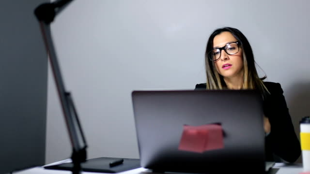 Young woman working on laptop video