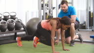 Young woman working out in gym under supervision of trainer video