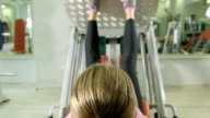 Young woman working out in health fitness club on leg press machine video