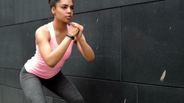 Young woman working out near a wall outdoors video