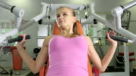 Young woman working out on chest press machine in health fitness center video