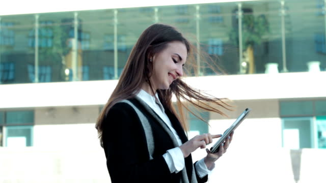 young woman works with mobile tablet on the street video