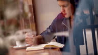 Young Woman Writing Journal at Window Seat in Coffee Shop video