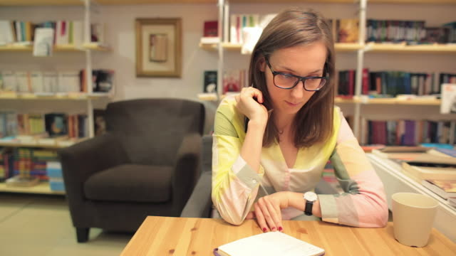 Young woman writting notes while drinking coffee. video