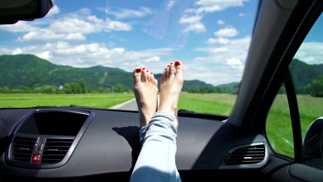 Young woman's feet with polished nails on a dashboard video