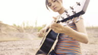 Young Woman's Hand Playing guitar. outdoors. video