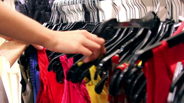Young Woman's Hands as she Shops for Dresses video