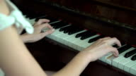 Young woman's hands playing the piano. Close up video