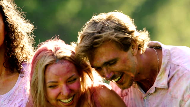 Young women and man in wet clothes and colorful powder laughing at Holi party video
