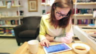 Young women architect working on table with digital tablet. video