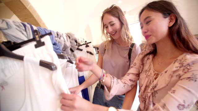 Young women choosing summer clothes to buy in clothing boutique video